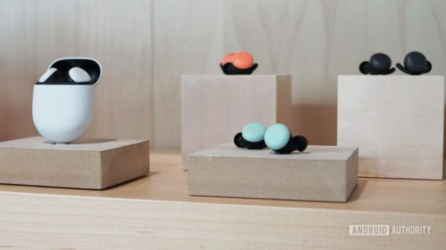 An image of the Google Pixel Buds in white, orange, light blue, and black all on a wood block display.