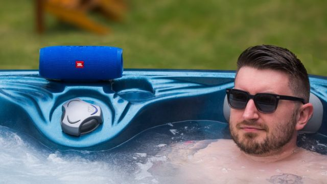 A photo of the JBL Charge 3, one of the best waterproof speakers, in use near a hot tub.
