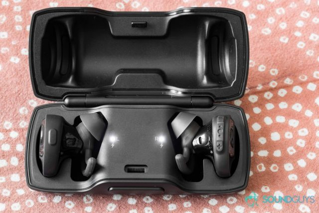A photo of the Bose SoundSport Free true wireless workout earbuds inside of the charging case with the LEDs alight.