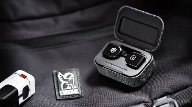 An image of the Master & Dynamic MW07 Go true wireless earbuds in the open charging case atop a Chrome Industries messenger bag.