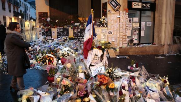 """Une femme contemple les fleurs et mots déposés à l\'entrée de la rue Nicolas-Appert, en hommage aux onze victimes de l\'attentat du 7 janvier 2015 dans les locaux de\""""Charlie Hebdo\""""."""