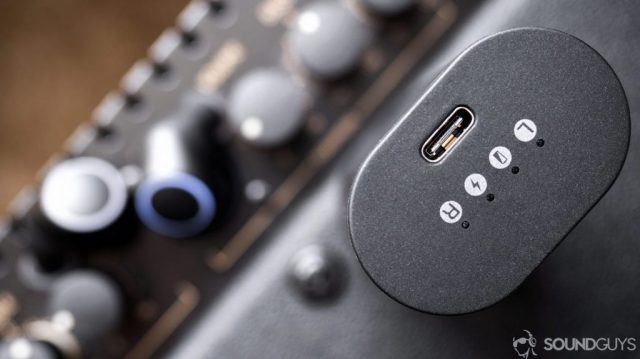 Top-down image of the Creative Outlier Air USB-C input on the charging case with the earbuds out of focus in the background.