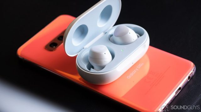 A picture of the Samsung Galaxy Buds earbuds in the case on top of a Samsung Galaxy S10e in Flamingo Pink.