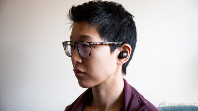 A picture of the JLab JBuds Air Icon true wireless earbuds worn by a woman looking to the left of the frame.