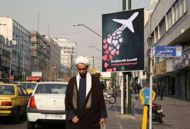 Un Iranien passe devant une affiche en mémoire des passagers du vol PS752 de la compagnie Ukraine International Airlines (UIA), qui s'est écrasé le8janvier près de Téhéran.