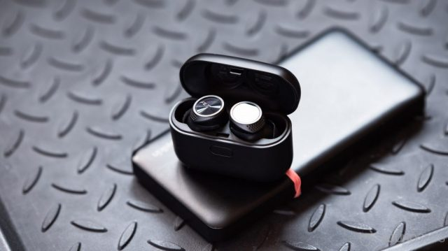 A picture of the Plantronics BackBeat Pro 5100 true wireless earbuds in the provided case, both are black.