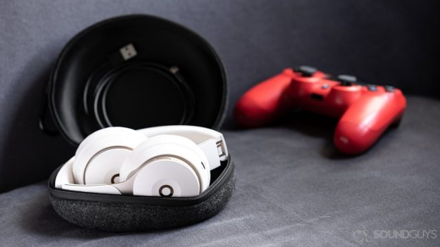 A photo of the Beats Solo Pro on-ear noise cancelling headphones folded in the cloth carrying pouch with the included Lightning cable and a PS4 controller (red) in the background.