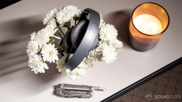 A picture of the Beats Solo3 Wirless headphones folded atop a bed of flowers with a candle and multitool.
