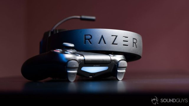 Razer gaming headsets, the Kraken X leaning against a PS4 controller with the headband facing the lens to show the Razer logo.