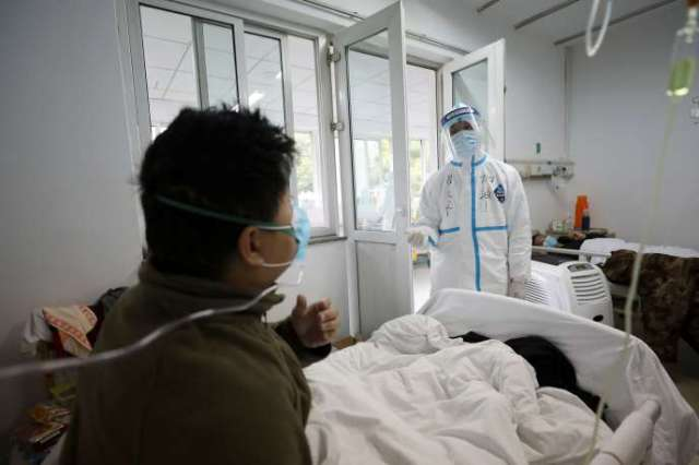 Un employé médical assiste un patient dans un service isolé de l'hôpital de Wuhan, Chine, le 13 février.