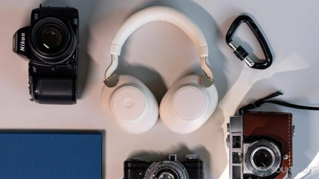 Aerial image of the Jabra Elite 85h headphones folded flat on a table and surrounded by vintage cameras, a blue notebook, and a black carabiner.