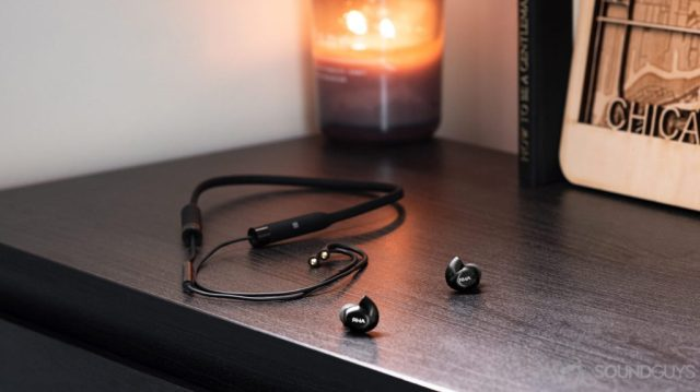 A photo of the RHA T20 Wireless earbuds detached from the wireless neckband on a wood surface with a candle in the background.