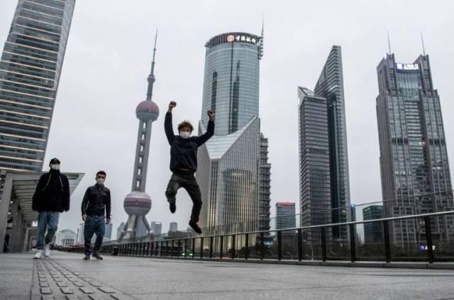 Trois personnes masquées dans le quartier des affaires de Shanghai, le 8 février 2020 ( AFP / NOEL CELIS )