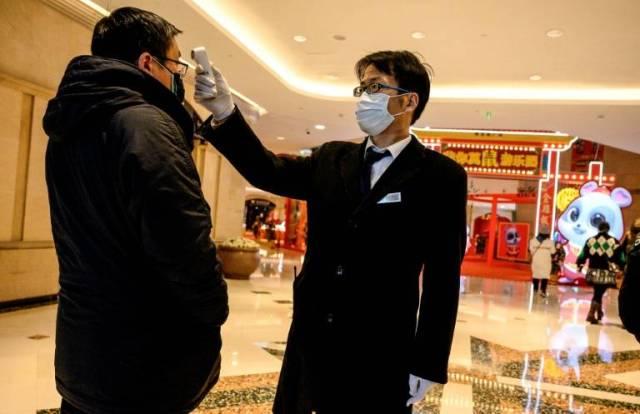 Un agent de sécurité prend la température d'un homme à l'entrée d'un centre commercial à Shanghai, le 8 février 2020 ( AFP / NOEL CELIS )