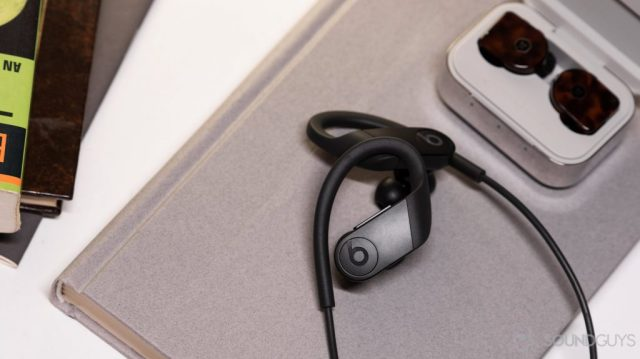 A picture of the Apple Beats Powerbeats on a book and next to the Master & Dynamic MW07 Plus true wireless noise cancellinlg earphones.