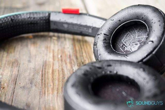 Best headphones under $200: The Plantronics BackBeat 500 FIT lying flat on a wood surface with water on the ear cups.