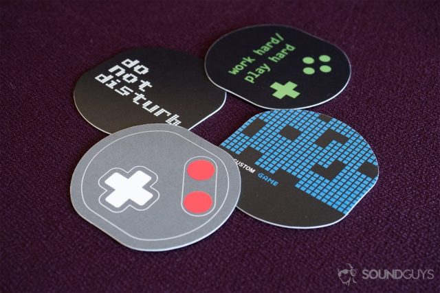 """Beyerdyanamic CUSTOM Game: The four panels are overlayed in groups of two. The top one is a blue, gridded pattern; the next one reads, """"do not disturb;"""" followed by a controller reminiscent of a Gameboy Color; and finally the last one reads, """"work hard/play hard."""""""