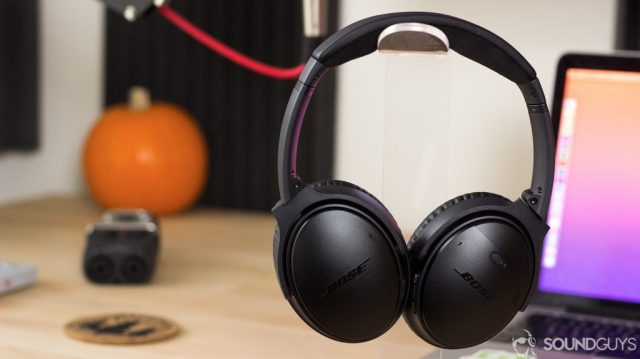 The Bose QuietComfort 35 II hanging on a headphone stand on a desk with a computer and pumpkin in the background.