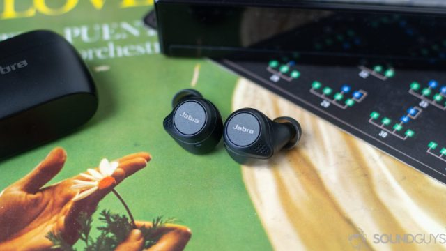 Close-up shot of the Jabra Elite 75t earbuds playback buttons on an old record