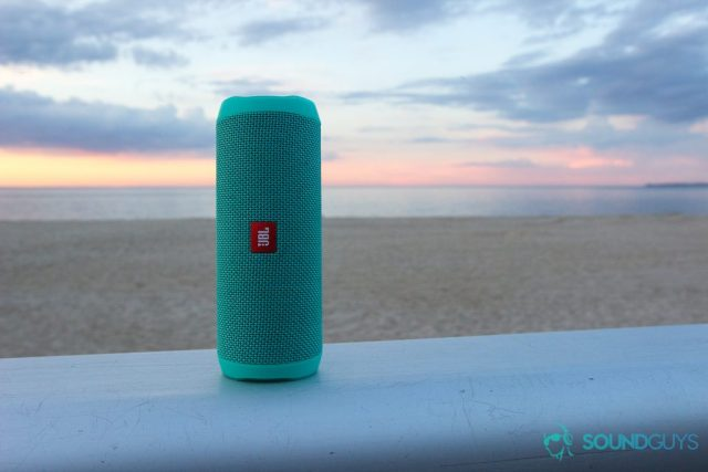 The mint colored JBL Flip 4 pictured against the sunset at the beach.