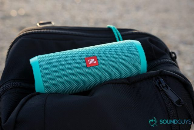 The teal JBL Flip 4 pictured on top of a black backpack.