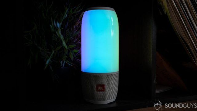 Shot of the JBL Pulse 3 in the dark in front of plants.