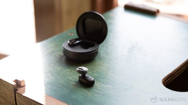 A photo of the LG Tone Free HBS FL7 true wireless earbuds nozzle-up on a wood surface.