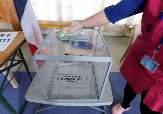 Une employée nettoie l'urne destinée au scrutin des élections municipales prévues dimanche, dans un bureau de vote à Nice, samedi 14 mars.