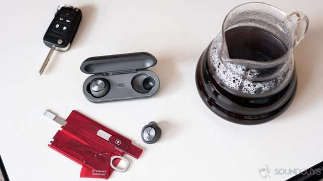 A photo of the Sol Republic Amps Air Plus true wireless noise cancelling earbuds on a coffee table with car keys and a multifunction card on it.