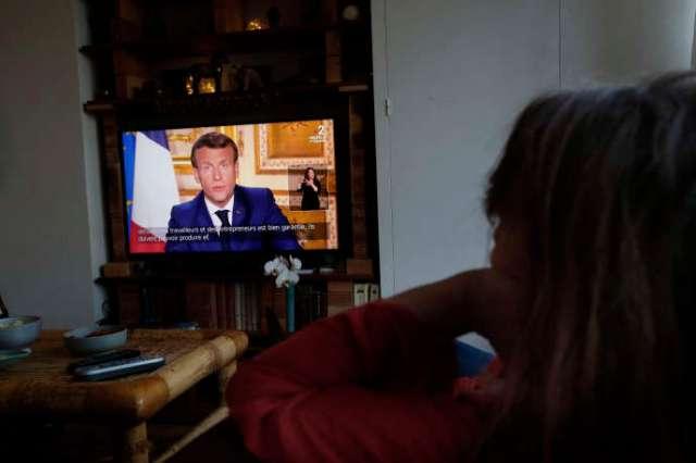 Une femme regarde l'allocution télévisée d'Emmanuel Macron depuis l'Élysée, le 13 avril à Avray (Hauts-de-Seine).