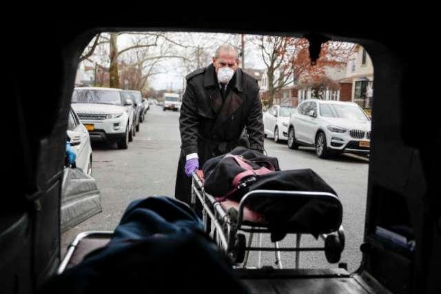 Tom Cheeseman charge le corps d'une victime du Covid-19dans sa camionnette, dans le quartier de Brooklyn à New York, le 3 avril.