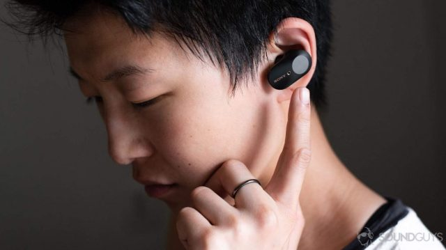 A photo of a woman wearing and reaching for the left earbud touch panel of the Sony WF-1000XM3, which costs as much as the original HiFiMan TWS600 retail price.