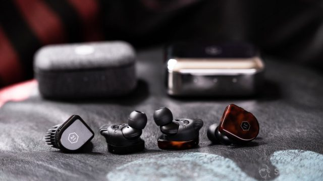 A picture of the Master & Dynamic MW07 Plus and MW07 Go noise canceling true wireless earbuds and charging cases next to each other on a leather surface.