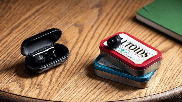 A picture of the Anker SoundCore Liberty Neo true wireless earbuds with one in the charging case and the other atop two stacked Altoids tins.