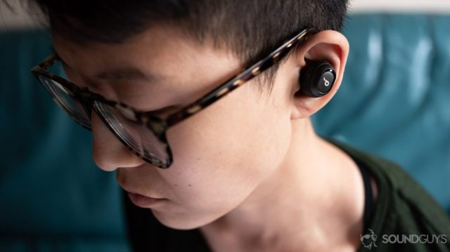A picture of the Anker SoundCore Liberty Neo true wireless earbuds worn by a woman looking down.