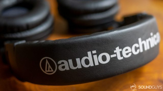 A photo of the Audio-Technica ATH-M50xBT on a wooden desk.