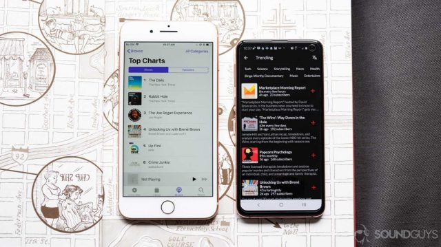 A picture of Apple Podcasts open on an iPhone 8 Plus next to the PlayFM app open on a Samsung Galaxy S10e on top of an open book.