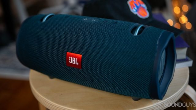 Close up of the blue JBL Xtreme 2 speaker on a wooden stool with a hat in the background.