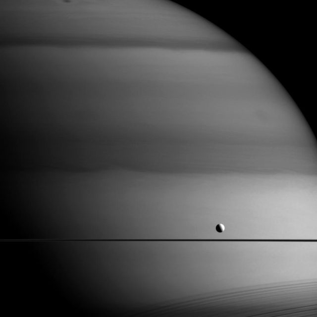small moon dione above a saturn ring against a field of saturn