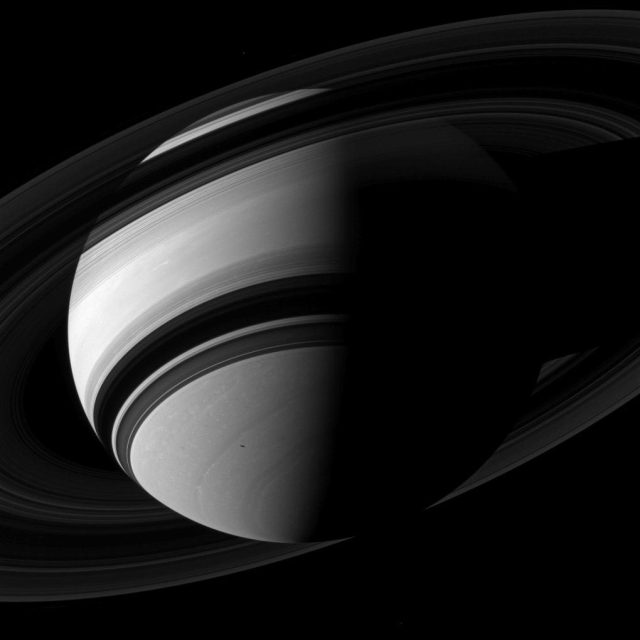 saturn and its rings from below with Mimas moon as a small dot