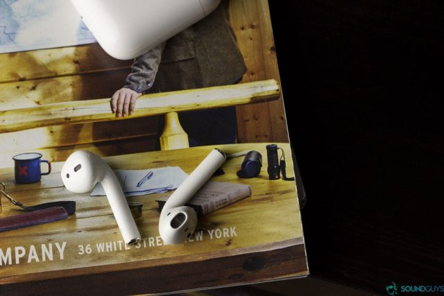 Best AirPods accessories - Pictured: Apple Earpods laid on a magazine page with the small carrying case at the top portion of the image.