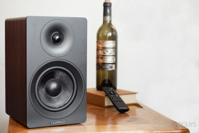 Fluance Ai40 review: The passive speaker on a table with a wine bottle in the background and the remote.