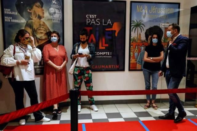 Des spectateurs attendent la première séance après la réouverture dans un cinéma de Paris, dans la nuit du 21 au 22 juin 2020 ( AFP / Abdulmonam Eassa )