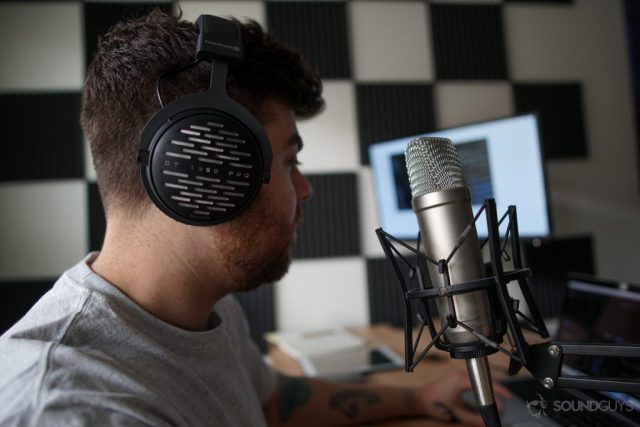 Man wearing Beyerdynamic headphones while using the Rode NT1-A microphone with foam padding on the wall in the background.