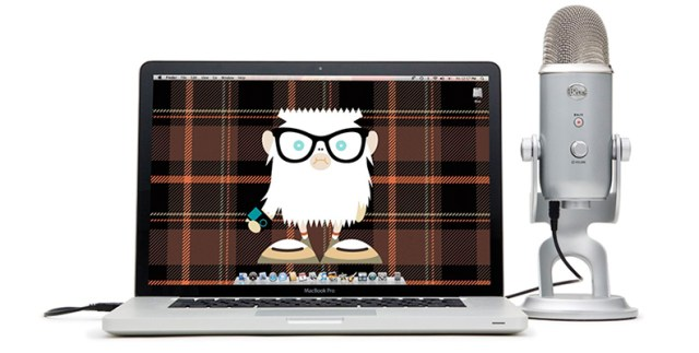 Amazon image of the Blue Yeti microphone next to a laptop with a cartoon owl as a desktop background.