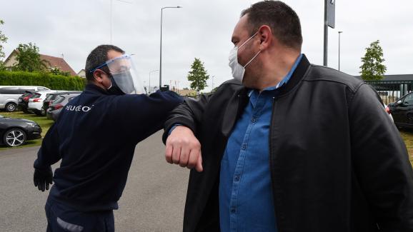 Un concessionnaire automobile et un client se saluent du coude, lors de l\'épidémie de Covid-19, le 4 mai 2020 à Illiers-Combray (Eure-et-Loir).
