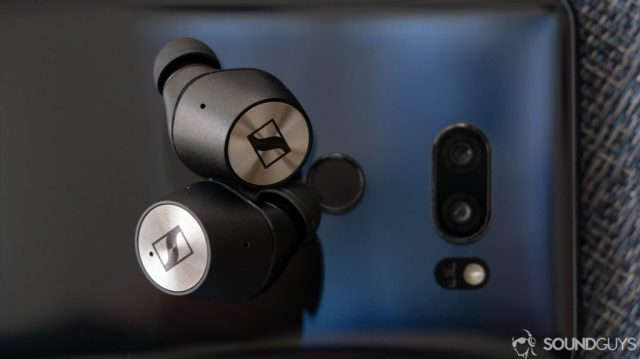 A photo of the Sennheiser Momentum True Wireless earbuds resting atop a phone.