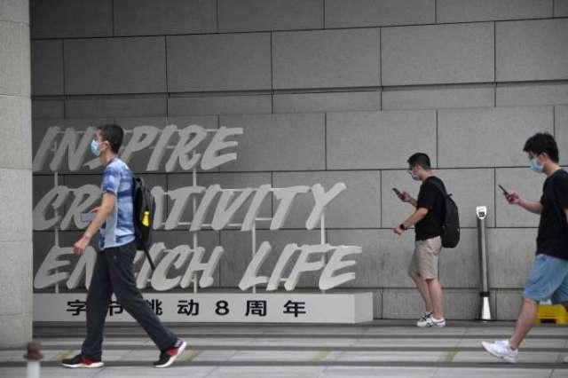 Les employés marchent devant le siège de ByteDance, le propriétaire de l'application de partage de vidéos TikTok, à Pékin le 5 août.