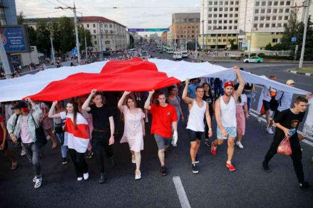 L'ancien drapeau national est déployé lors d'un rassemblement de l'opposition, le 16 août à Minsk (Biélorussie).