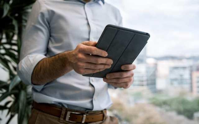 Man holding iPad outdoors